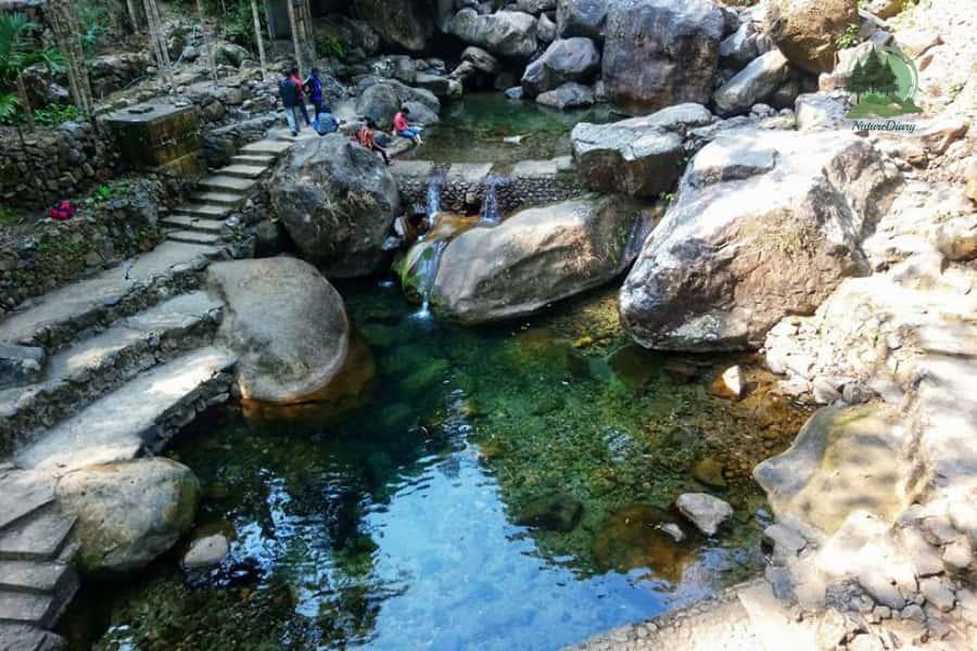 pool under double decker living root bridge